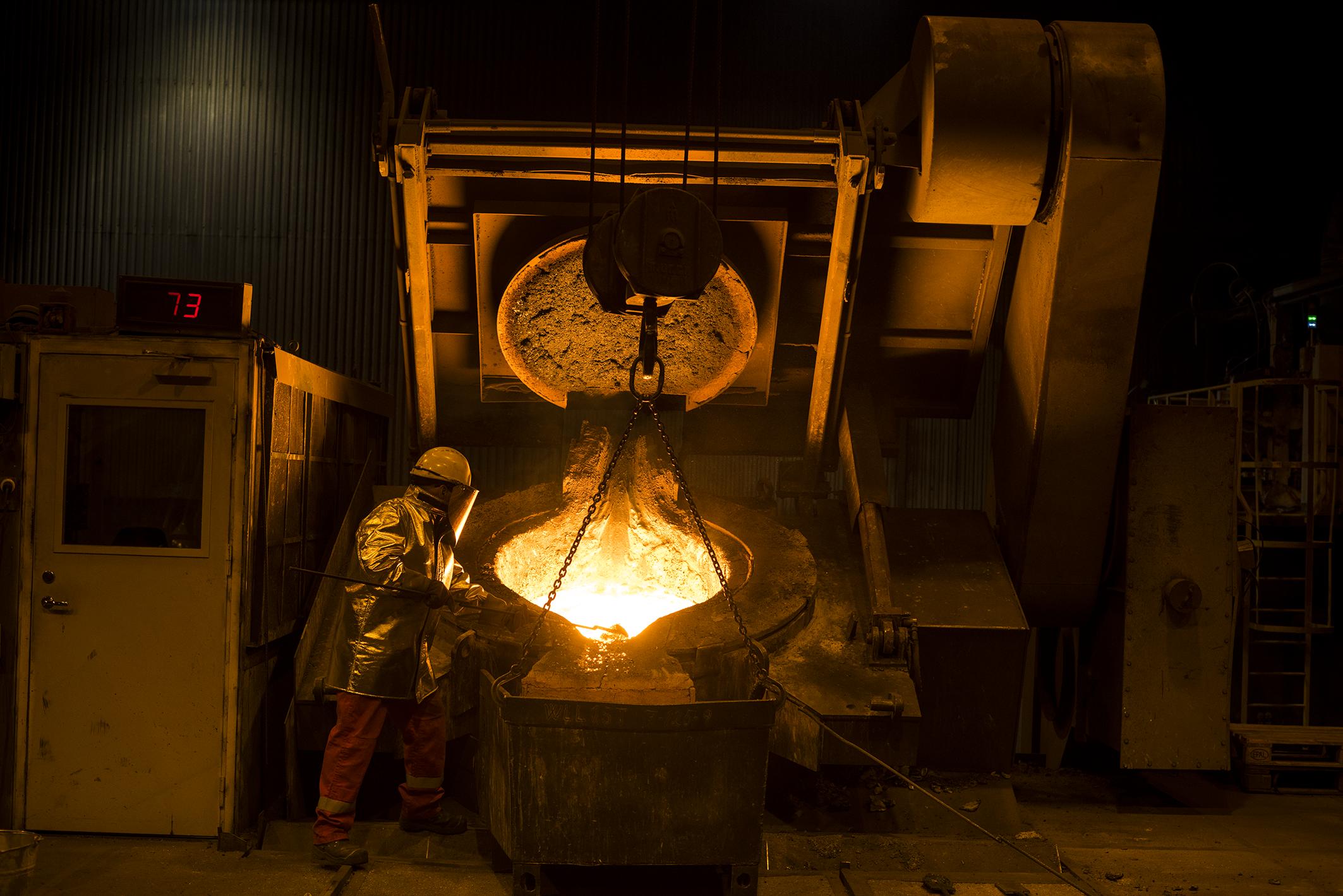 En jernverksarbeider fjerner slagg fra smeltet jernskrap.