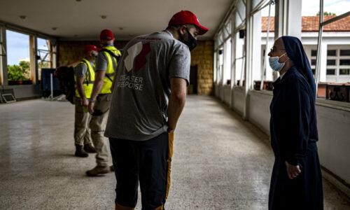 En frivillig fra Team Rubicon slår av en prat med en nonne. Skolen hun jobber på fikk alle vinduene ødelagt under eksplosjonen.